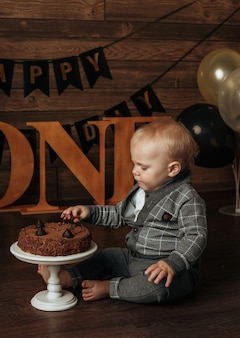 A birthday boy in a gray suit eats a chocolate cake on a brown background