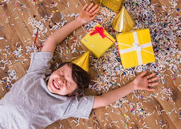 Birthday boy making funny face in party hat lying on floor with gifts and confetti
