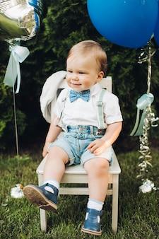屋外の椅子に誕生日の男の子