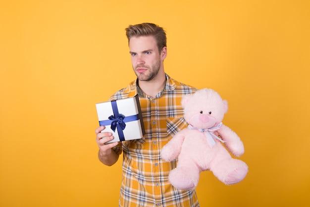 생일 소년. 긍정적 인 분위기. 귀여운 테디베어 장난감. 부드러움 부드러움. 발렌타인 데이 선물. 남자 포옹 부드러운 장난감입니다. 깜짝 개념을 만드십시오. 귀엽고 낭만적입니다. 수염난 힙스터는 장난감 노란색 배경을 재생합니다.