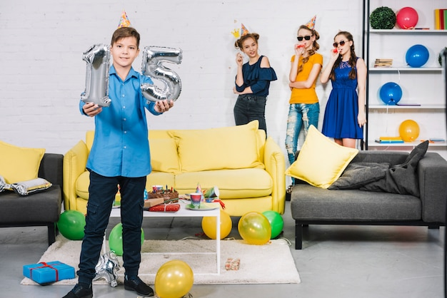A birthday boy showing numeral 15 foil silver balloons with his friends standing at the background
