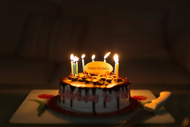 Birthday cake on black table with colorful candles lit.