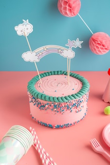 Birthday cake for boys and girls with glasses and paper straws for a party