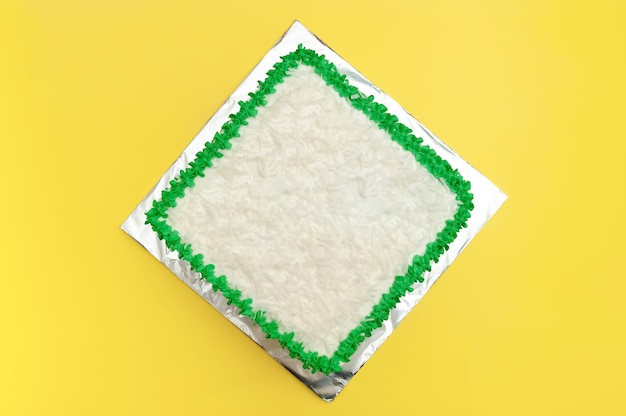 Birthday cake decorated with green icing and grated coconut isolated on yellow background