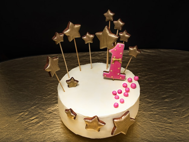 Birthday cake decorated with pink number 1 and gold stars of gingerbread on a dark