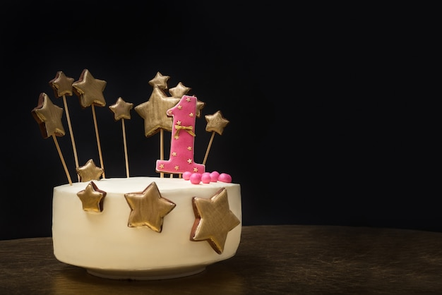 Birthday cake decorated with pink number 1 and gold stars of gingerbread