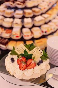 甘いテーブルの前景にイチゴ、ミント、チョコレートで飾られたバースデーケーキ。結婚式のイベント。ホテルでの食事。お祝いのイベント。味と喜び。レクリエーションと娯楽。