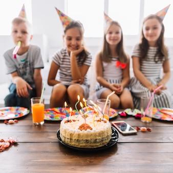 Birthday cake near blurred kids