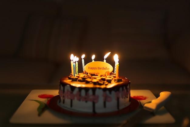 Именинный торт на черном столе с красочными зажженными свечами.
