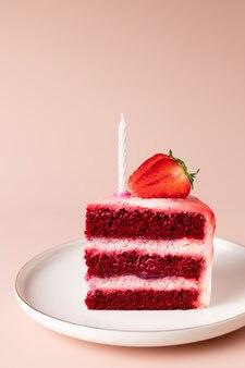 新鮮なイチゴで飾られたキャンドルとバースデーケーキのスライス