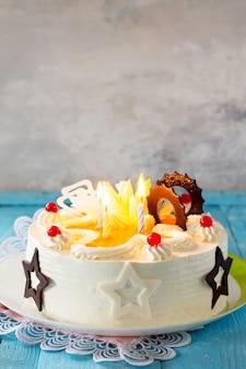 파란색 배경 복사 공간에 화려한 초를 넣은 휘핑 크림이 있는 생일 케이크 스폰지 케이크