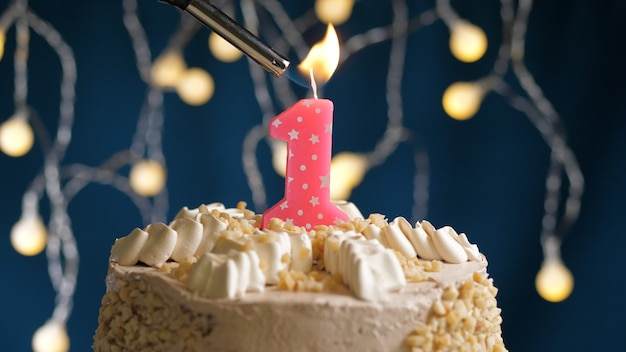 Birthday cake with 1 number pink candle on blue backgraund set on fire by lighter. close-up view
