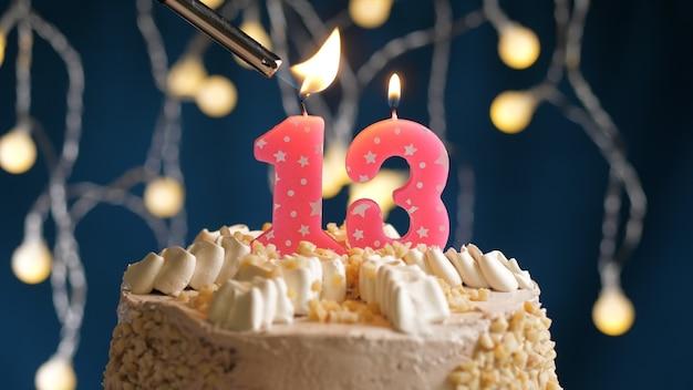 ライターで火をつけた青い背景に13番のピンクのキャンドルが付いたバースデーケーキ。クローズアップビュー