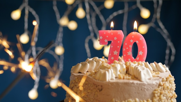 Birthday cake with 70 number pink candles and burning sparkler on blue backgraund. close-up
