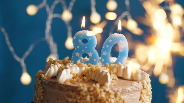 Birthday cake with 80 number candles and burning sparkler