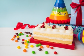 Birthday cake with candies; hat; and presents on table against blue backdrop