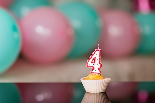 Торт на день рождения со свечой и разноцветных шаров на фоне