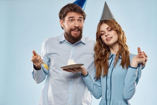 キャンドルの男性と女性の企業パーティーの楽しい休日とバースデーケーキ。