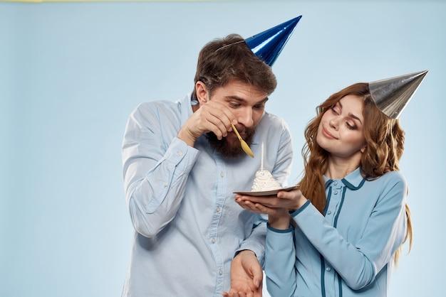 キャンドルの男性と女性の企業パーティーの楽しい休日とバースデーケーキ