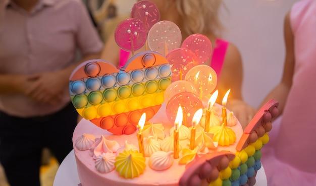 キャンドルとバースデーケーキ休日のケーキケーキにキャンドルキャンドルとイチゴの美しい白いケーキ...