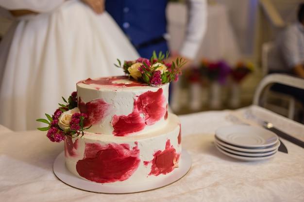 キャンドルとバースデーケーキ。ケーキの上のろうそく。休日のケーキ。暗い背景にイチゴと美しい白いケーキ。縦の写真。