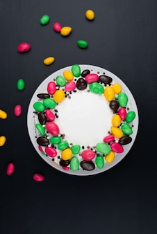 Birthday cake with cream and candy decor on a black surface