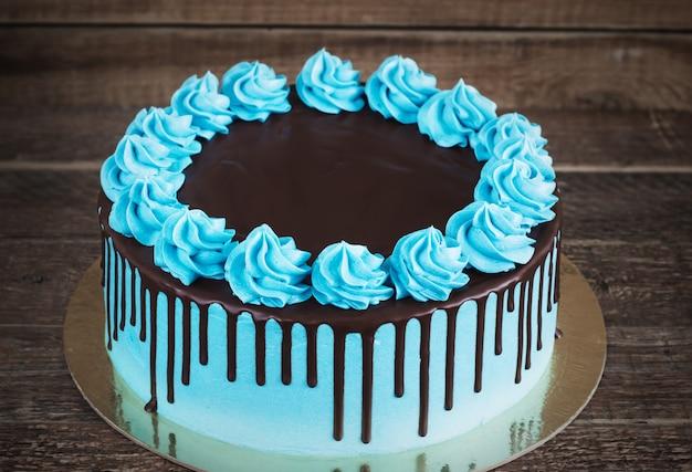 Birthday cake with cream chocolate drips on a dark wooden