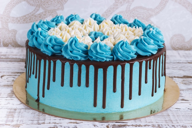 Birthday cake with cream chocolate drips on a white