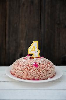나무 테이블에 4 개의 번호가 매겨진 촛불 생일 케이크