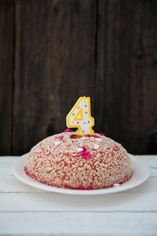 Birthday cake with four numbered candle on wooden table