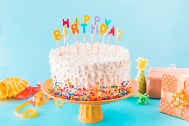 Birthday cake with gift and accessories on blue background