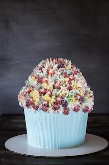 회색 배경에 꽃 장식 생일 케이크입니다. 어머니의 날, 첫 생일.