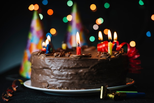 Birthday cake with an illuminated candle against light backdrop and party hat