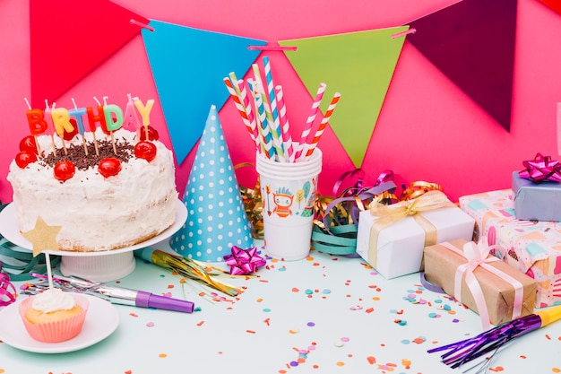 Birthday cake with party accessories and confetti on blue background