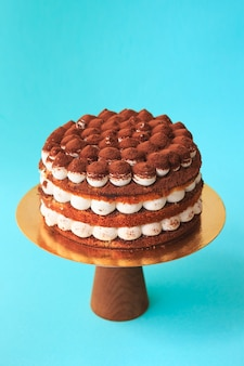 Birthday cake on the wooden cake stand. beautiful chocolate sponge cake with whipped cream garnished with sprinkled cocoa. blue background. copy space. food photography for recipe.