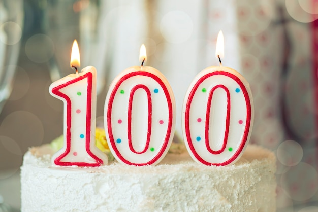 Birthday candle as number one hundred on top of sweet cake on the table, 100th birthday