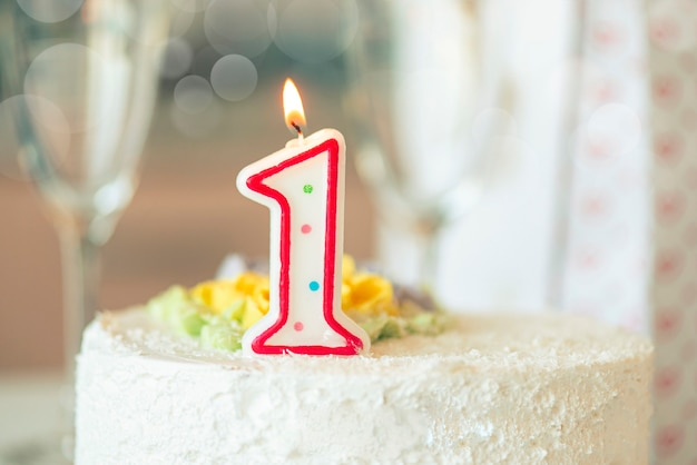 Birthday candle as number one  on top of sweet cake on the table, concept picture