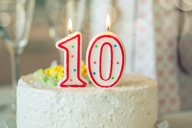Birthday candle as number ten 10 on top of sweet cake on the table, 10th birthday