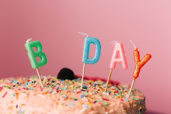 Birthday candles on cake against colored background