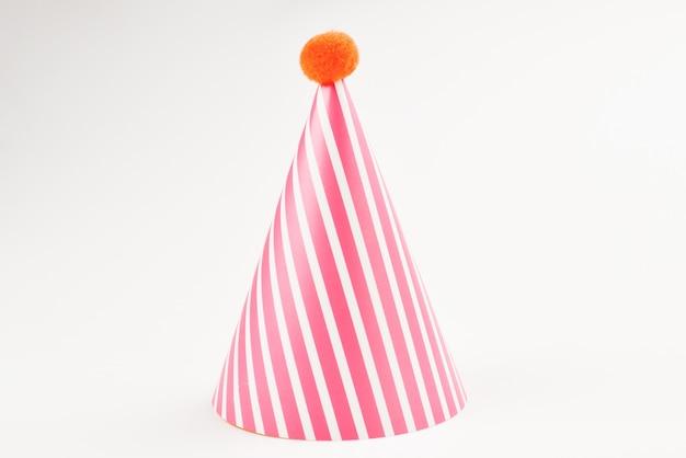 白い表面に分離された誕生日の帽子