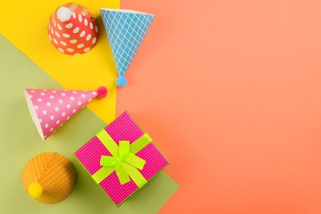 誕生日の帽子と緑の背景にプレゼント、紙吹雪。テキストまたはデザインのためのスペース。