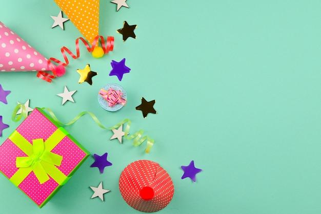 誕生日の帽子とプレゼント、緑の背景に紙吹雪。テキストやデザインのためのスペース。
