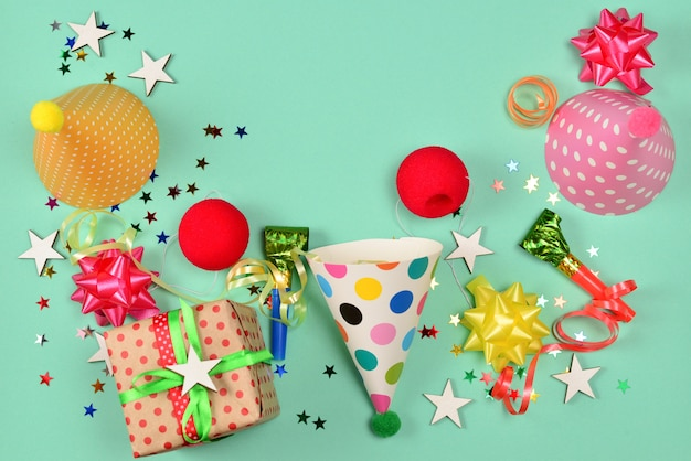 Шапки на день рождения, подарок, конфетти, ленты, звезды, носы клоуна на зеленом фоне. место для текста или дизайна.