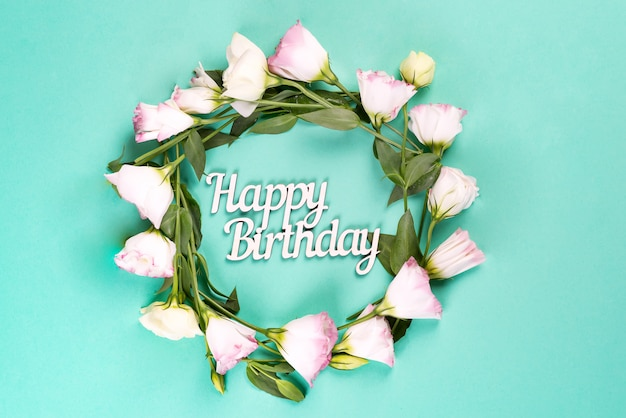 Birthday card. wreath made of pink flowers eustoma on blue surface