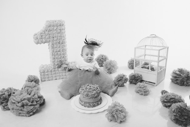 Birthday celebration: girl sitting on the floor among the numbers 1, artificial flowers and bird cage