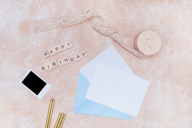 Birthday celebration supplies on pink marble background