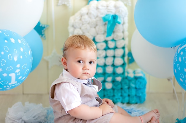 誕生日の子供1歳の男の子、スーツケースと蝶ネクタイでボールとナンバーワンで座っている赤ちゃん