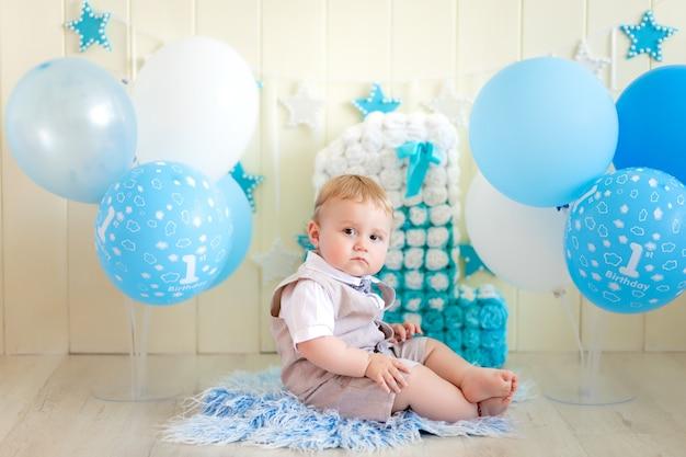 День рождения ребенка 1 год, мальчик, сидящий с шариками и номер один в костюме и галстуке-бабочке