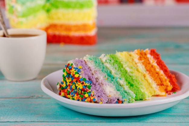 Birthday colorful rainbow cake with cup of coffee and knife.
