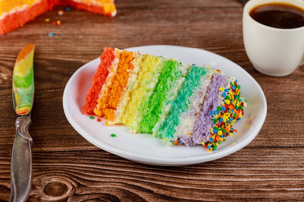 Birthday colorful rainbow layer cake with cup of coffee and knife.